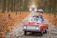 Pojke som kör med hans bil Arkivfoto