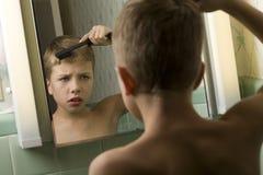 pojke som kammar hår hans barn Royaltyfria Foton