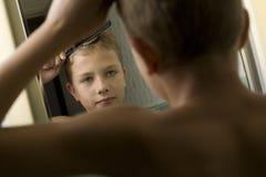 pojke som kammar hår hans barn Arkivfoton