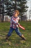 Pojke som kastar en frisbee Fotografering för Bildbyråer