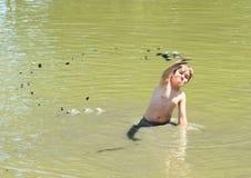Pojke som kastar gyttja i vatten Royaltyfri Fotografi