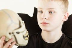 Pojke som kläs som den hållande skallen för trollkarl Arkivbilder