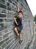 Pojke som klättrar den svarta tegelstenväggen Arkivfoton