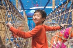 Pojke som klättrar det netto på inomhus playround och leenden royaltyfri foto