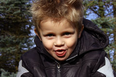 pojke som klibbar ut toungue Arkivbild