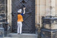 Pojke som knackar i dörrknackare på gammal medeltida slott Royaltyfri Bild