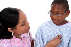 pojke som kontrollerar för sjuksköterskafotografi s för bröstkorg det lyssnande materielet till Arkivbild