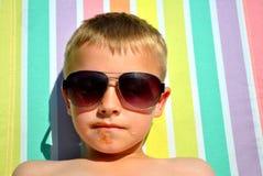 Pojke som kopplar av på solsängen Arkivfoto