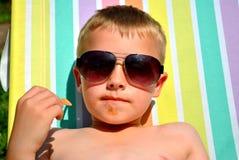 Pojke som kopplar av på solsängen Arkivbild