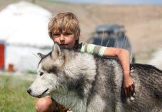 Pojke som kramar en fluffig hund royaltyfri fotografi