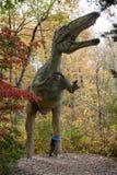 Pojke som kramar en i naturlig storlek dinosaurie Royaltyfri Foto
