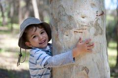 pojke som kramar treen Arkivfoto