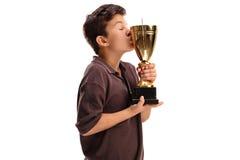 Pojke som kysser en guld- trofé Arkivfoton