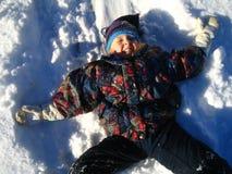 pojke som lägger snow arkivfoto