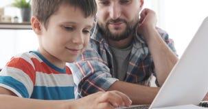 Pojke som lär att använda bärbara datorn med fadern hemma lager videofilmer