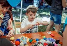Pojke som lär att göra färgrika tabellservetter på handarbeteseminariet Royaltyfri Bild
