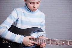 Pojke som lär att spela en elektrisk gitarr Musik, hobby och leisur royaltyfri fotografi