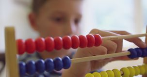 Pojke som lär matematik med kulrammet i ett bekvämt hem 4k lager videofilmer