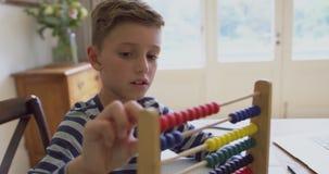 Pojke som lär matematik på kulrammet på tabellen i ett bekvämt hem 4k arkivfilmer