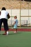 pojke som lärer tennis Arkivfoto