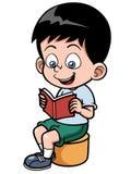 Pojke som läser en bok Royaltyfria Bilder