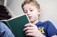 Pojke som läser en bok Arkivbild