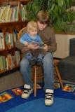 pojke som läser till litet barn Royaltyfria Bilder