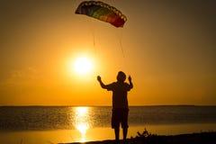 Pojke som lanserar regnbågedraken på solnedgången Royaltyfri Foto