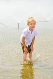 Pojke som leker i springbrunnen Arkivbild