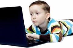 Pojken som ser bärbar dator, övervakar Royaltyfria Bilder