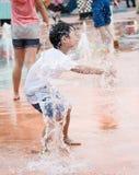 Pojke som leker med sprejande vatten Arkivfoto