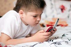 Pojke som leker på celltelefoner Arkivbilder