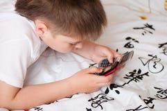 Pojke som leker på celltelefoner Royaltyfria Foton