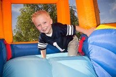 Pojke som leker på, och uppblåsbar glidbana Royaltyfri Bild