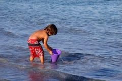 Pojke som leker på stranden. Arkivbild