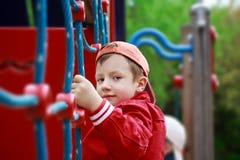 Pojke som ler på klätterställningen arkivfoton
