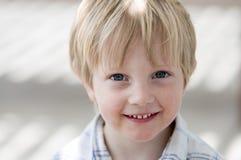 Pojke som ler på tittaren Royaltyfria Bilder