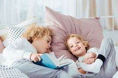 Pojke som ligger med boken royaltyfria foton