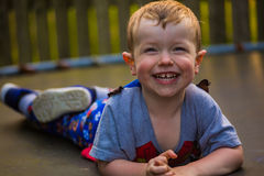 Pojke som ligger på att skratta för trampolin Arkivfoto