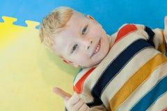 Pojke som ligger på den färgglade krogshowtummen upp royaltyfri bild