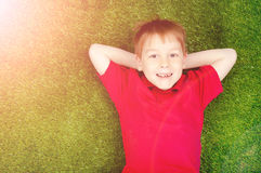 Pojke som ligger på en grön gräsmatta arkivfoto