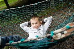 Pojke som ligger på en hängmatta Fotografering för Bildbyråer