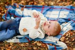 Pojke som ligger på filten bland de gula sidorna, arkivfoto