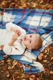 Pojke som ligger på filten bland de gula sidorna, fotografering för bildbyråer