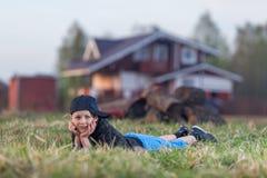 Pojke som ligger på gräset Arkivbild
