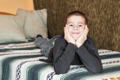 Pojke som ligger på säng Royaltyfri Foto