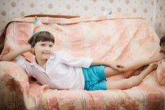 Pojke som ligger på soffan och poserar för foto Arkivbild