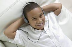 Pojke som ligger på soffan som lyssnar till musik på över huvudet sikt för hörlurarstående Arkivfoton
