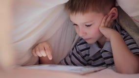 Pojke som ligger under filten och hållande ögonen på tecknad film på handlagblocket arkivfilmer