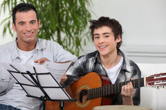 Pojke som lärer att play gitarren Fotografering för Bildbyråer